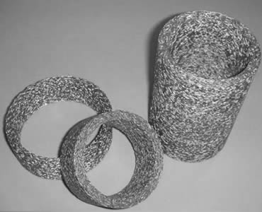 Three cylindrical knitted wire mesh filters.