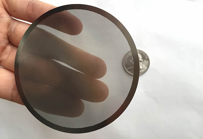 A hand is touching a piece of translucent perforated round filter disc. Under the disc, there is a metal coin.