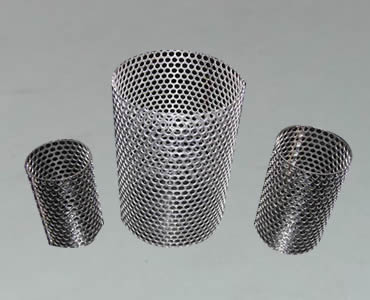 Three perforated filter tubes with oval perforated holes stand on black ground.