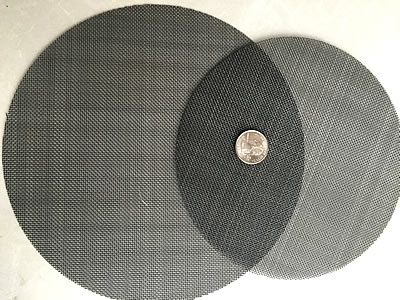 Two black wire cloth filter discs are placed together with a metal coin in the middle.