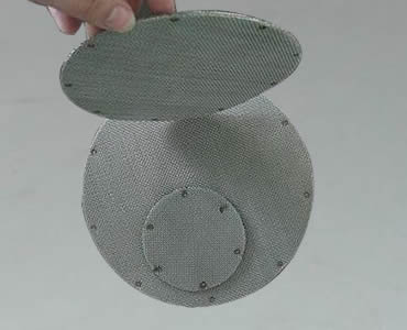 Two circular spot welded filter packs flat on ground and another circular filter disc upright on them.