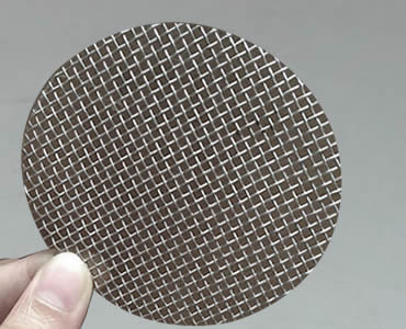 Two fingers hold a single layer filter disc made of stainless steel mesh and without framed edge.